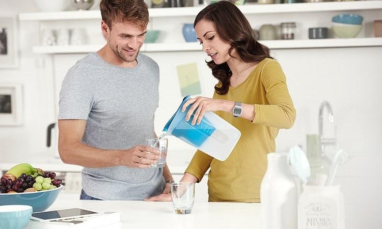 女性が男性に浄水器の水を注いでいるシーン